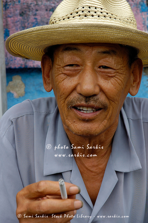 Portrait of a man wearing a hat and smoking a cigarette in Datong, Shanxi, China.