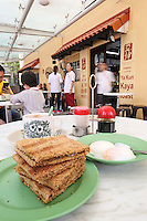 Standard set of kaya toast, 2 soft boiled eggs and tea, black sauce and pepper for eggs at the popular breakfast cafe chain Yakun Kaya Toast in Singapore.