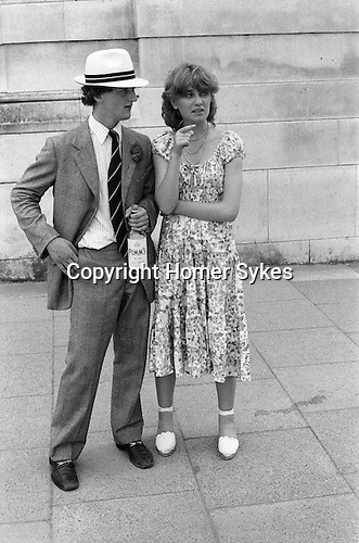 St Johns Wood, London. 1978 <br /> With a bottle of Pimm's No1 in hand an old Harrovian and his girlfriend make their way to the annual Eton v Harrow cricket match at Lords. He's looking posh in a Panama straw hat, and Prince of Wales Check suit and loafers. She's wearing a Laura Ashleyesque floral dress and espadrilles.
