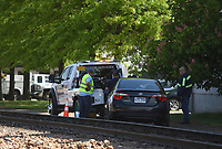Kevin Dickson (from left), Ryan Wardow and Tory Harmon secure a car to a tow truck, Monday, May 3, 2021 near the train tracks on Walnut Street and South Arkansas Street in Rogers. Rogers Police received a call at 9:29 am on Monday for a single car collision with a train. One person was admitted to the hospital, but his condition is unknown. Check out nwaonline.com/210504Daily/ for today's photo gallery. <br /> (NWA Democrat-Gazette/Charlie Kaijo)