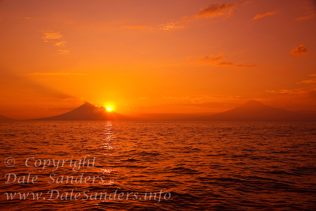 """The morning sun rising behind a couple of distant volcano's... as seen from a dive site in the Fathers Reefs off New Britain Island, Papua New Guinea. A small tendril of steam rising from the 2,334 meter high summit of Mount Ulawan is a gentle reminder that we are diving in Papua New Guinea's  """"Ring of Fire"""".  Papua New Guinea has over sixty volcanoes strewn across its vast archipelago… nineteen exist on New Britain Island alone… and five of those are currently active."""