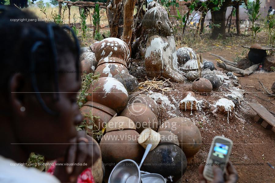 BURKINA FASO , Gaoua, Kampti, Lobi culture, Lobi is an ethnic group and they are animist and worship ancestor spirit, village KWEKWERA ( KOUEKOUERA ), court of fetish maker DA LEPIRTHE, fetish figure made from clay, woman with mobile phone / Lobi Ethnie, Lobi sind Animisten und praktizieren Ahnenkulte, Dorf KWEKWERA ( KOUEKOUERA ), am Hof des Fetischmeister DA LEPIRTHE, Fetisch Figur aus Lehm, Frau mit Mobiltelefon