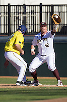 Texas State Bobcats first baseman Tanner Hill (42) catches a pickoff attempt during the NCAA season opening baseball game against the Michigan Wolverines on February 14, 2014 at Bobcat Ballpark in San Marcos, Texas. Texas State defeated Michigan 8-7 in 10 innings. (Andrew Woolley/Four Seam Images)
