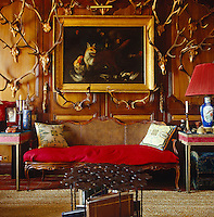 A cane-backed antique sofa has been covered with a bright red woollen blanket creating an informal, warm and cosy note in the private living room