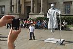 "Tourists Trafalgar Square London Uk, child has photograph taken next to a levitated ""Living Statue""."