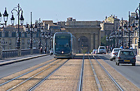 The old bridge Pont de Pierre. Porte Bourgogne or des Salinieres. The modern tram. Bordeaux city, Aquitaine, Gironde, France