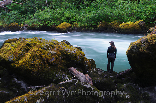 Hiker standing beside the Elwah River in Olympic National Park. Washington.