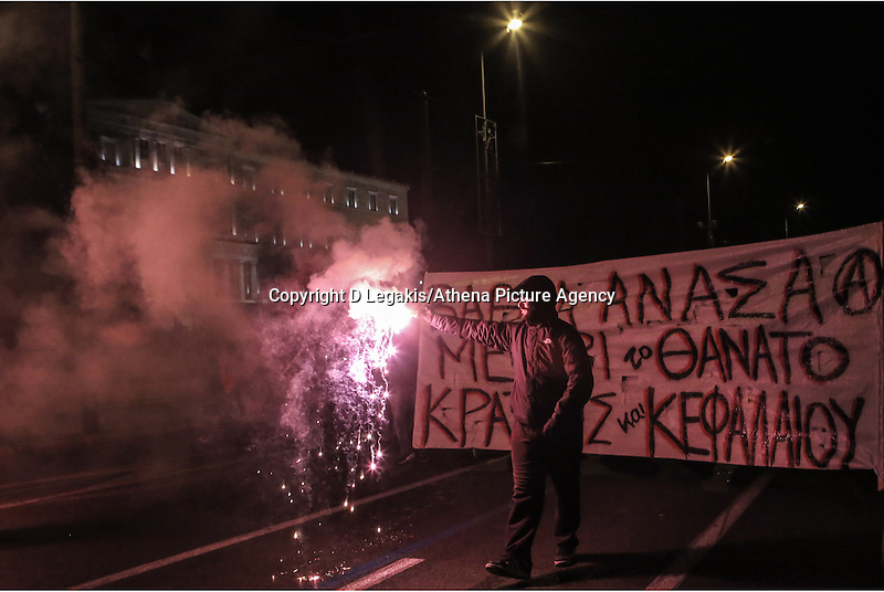 """Pictured: Protesters in helmets and armed with wooden bats and flares holding a slogan reading """"Deep breath until the death of  capitalism and state"""" walk past the Greek Parliament Tuesday 02 December 2014<br /> Re: At least 15 people have been arrested after a peaceful support rally for jailed hunger strike anarchist turned into violent confrontation with police. Authorities used tear gas and stun grenades to quell rioters carrying Molotov cocktails.<br /> As an estimated between 8,000 and 10,000 protesters marched through the central Athens shouting slogans in support of Nikos Romanos, the imprisoned anarchist who is staging a hunger strike as he demands the right to be able to attend university, anarchists' march got violent on the streets of Exarchia, downtown Athens."""