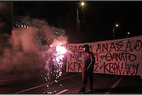 "Pictured: Protesters in helmets and armed with wooden bats and flares holding a slogan reading ""Deep breath until the death of  capitalism and state"" walk past the Greek Parliament Tuesday 02 December 2014<br />