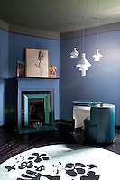 A 1970s vanity table and armchair is juxtaposed with a 20th century fireplace in this blue-painted guest bedroom