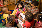 Day Care Center 2-3 year olds group of boys and girl playing with human figures and doll house
