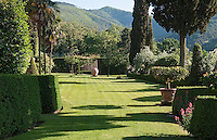 The formality of the garden gives way to the wooded hills of the surrounding Tuscan countryside
