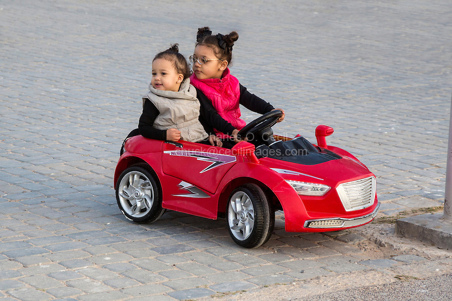 Essaouira, Morocco.  Girls Riding in Toy Car in the Place Moulay Hassan.