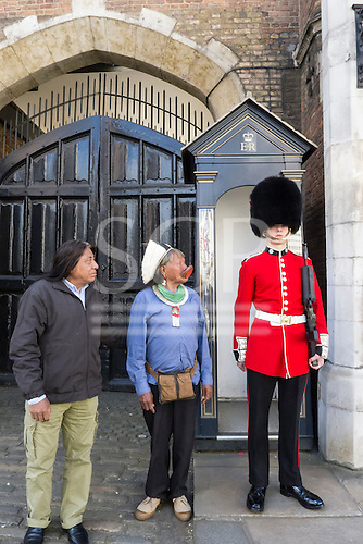 11 June 2014. Kayapo Chiefs Raoni Metuktire and Megaron Txucarramae during their visit to London. The chiefs stand next to a sentry box and looking at a Coldstream Guardsman in full scarlet uniform and bearskin.