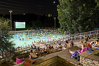 Deep Eddy Pool Splash Movie Night Pool-goers enjoy a movie from the grassy slope, concrete steps, or on an inner tubes for floating in the refreshing 70-degree water at Deep Eddy Pool in Austin, Texas.