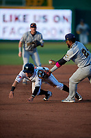 Lansing Lugnuts Rafael Lantigua (9) its tagged out by third baseman Kevin Maitan (24) during a Midwest League game against the Burlington Bees on July 18, 2019 at Cooley Law School Stadium in Lansing, Michigan.  Lansing defeated Burlington 5-4.  (Mike Janes/Four Seam Images)