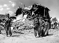 ROK military police pose before the ruins of a devastated building in Pohang.  Most buildings that housed red troops were destroyed.  October 17, 1950. (Navy)<br /> NARA FILE #:  080-G-420652<br /> WAR & CONFLICT BOOK #:  1502
