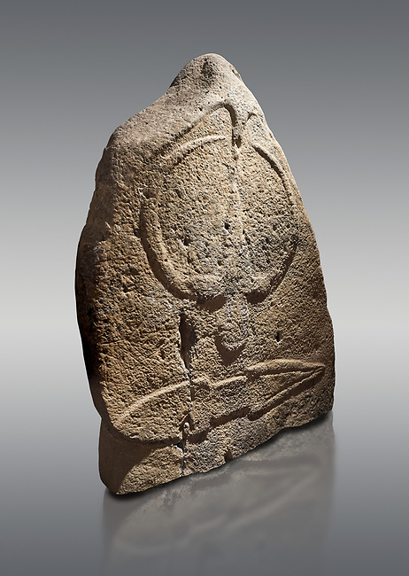 Late European Neolithic prehistoric Menhir standing stone with carvings on its face side. The representation of a stylalised male figure starts at the top with a long nose from which 2 eyebrows arch around the top of the stone. below this is a carving of a falling figure with head at the bottom and 2 curved arms encircling a body above. at the bottom is a carving of a dagger running horizontally across the menhir. Excavated from Barilli I site,  Laconi. Menhir Museum, Museo della Statuaria Prehistorica in Sardegna, Museum of Prehoistoric Sardinian Statues, Palazzo Aymerich, Laconi, Sardinia, Italy. Grey background.