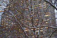 """Detail of The Woolworth Building (on the right side of the frame) Viewed Thru Snow Covered Trees Illuminated at Dusk, City Hall Park, Civic Center, Lower Manhattan, New York City, New York State, USA..<br /> <br /> The Woolworth Building at 233 Broadway was completed by the architect Cass Gilbert in 1913.  Built in the Neo-Gothic style with terra cotta detail, it was the tallest building in the world  (792 ft. high) until it was supersceded by The Chrysler Building on 42nd Street in 1930.  The building was the headquarters of the F.W. Woolworth and Co. chain of Five and Dime Stores.  When the building opened it was dubbed """"The Cathedral of Commerce"""" by the Brooklyn minister and radio evangelist Rev. S. Parkes Cadman."""