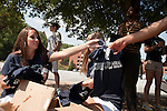 "August 20, 2011. Chapel Hill, NC.. Paris Flowe, left, a senior at UNC-CH and an American Eagle ""brand ambassador"", hands out t-shirts to volunteers who will help her spread awareness of the brand by helping incoming students with their stuff and giving away coupons on move in day.. Many companies have increased their efforts to reach the youth market by employing popular college students to raise the awareness of the brand by peer to peer marketing on campus' around the country."