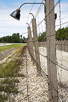Germany. Bayern state. The Dachau Concentration Camp Memorial Site. The camp fencing ( partly reconstructed in 1965) was made-up of grass, strips, ditches with an electrified barbed-wire fence and the camp wall. SS men guarded the camp grounds from seven towers. If a prisoner stepped onto the grass strip, he was shot at. On march 22, 1933, the first concentration camp was opened in Dachau by the Nazis. It became a model for all later concentration camps established under the control of the SS men and the Third  Reich. © 2007 Didier Ruef
