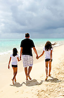 Jason holds the hands of daughter Leilani and Ke'alohi at the beach on the windward side of Oahu