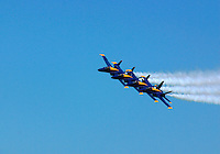The Blue Angels FA 18s fly in formation with trails of white smoke against a clear blue sky