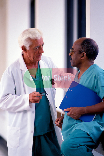 two doctors standing in hospital corridor discussing patient