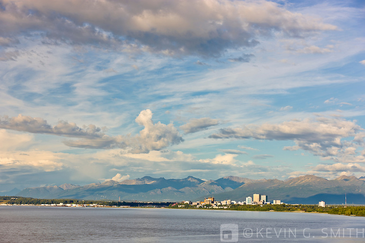 Thunderstorm clouds above the Anchorage city skyline  Knik Arm at high tide in the foreground, Chugach mountains in the background, afternoon light, Anchorage, Southcentral Alaska, Summer.