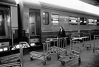 Italy. Lazio Region. Rome. Roma Termini (in Italian, Stazione Termini) is the main railway station of Rome. A religious nun walks on the railway platform before entering her train. Empty trolleys left over. Handicapped wheelchair access logo sign. Rome is the capital city and a special comune of Italy (named Comune di Roma Capitale), as well as the capital of the Lazio region. 1.06.92  © 1992 Didier Ruef