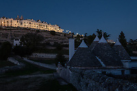 """Italy. Apulia Region. Locorotondo. View at night on the town and a group of Truli. A trullo (plural, trulli) is a traditional Apulian dry stone hut with a conical roof. The structural walls of a trullo are laid directly on the bedrock. Their width varies from 0.80 to 2.70 metres. Their height (from ground level to where the vault starts) ranges from 1.60 to 2 metres. On cone's top, there is normally a hand-worked sandstone pinnacle (pinnacolo), that may be one of many designs - disk, ball, cone, bowl, polyhedron, or a combination thereof, that is supposed to be the signature of the stonemason who built the trullo. Their style of construction is specific to the Itria Valley in the Murge area. Trulli generally were constructed as temporary field shelters and storehouses or, as permanent dwellings by small proprietors or agricultural labourers. Trullo has replaced the local term casedda which was used by locals in the Murgia area to call this type of house, which used to be the local agricultural dry stone hut. Locorotondo is a town and comune with a population of about 14,000. The city is known for its circular structure which is now a historical center, from which derives its name, which means """"Round place"""". Apulia (Puglia) is a region in Southern Italy. 5.12.18  © 2018 Didier Ruef"""