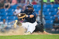 Helena Brewers catcher Payton Henry (33) waits for the throw as J.J. Muno (2) of the Great Falls Voyagers slides head first into home plate at Centene Stadium on August 18, 2017 in Helena, Montana.  The Voyagers defeated the Brewers 10-7.  (Brian Westerholt/Four Seam Images)