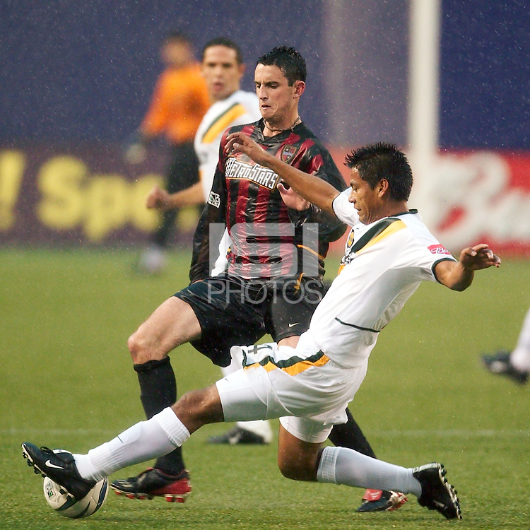 Jose Retiz of the Galaxy goes for a tackle on Mark Lisi of the MetroStars. The LA Galaxy lost to the NY/NJ MetroStars 1-0 on 6/21/03 at Giant's Stadium, NJ..