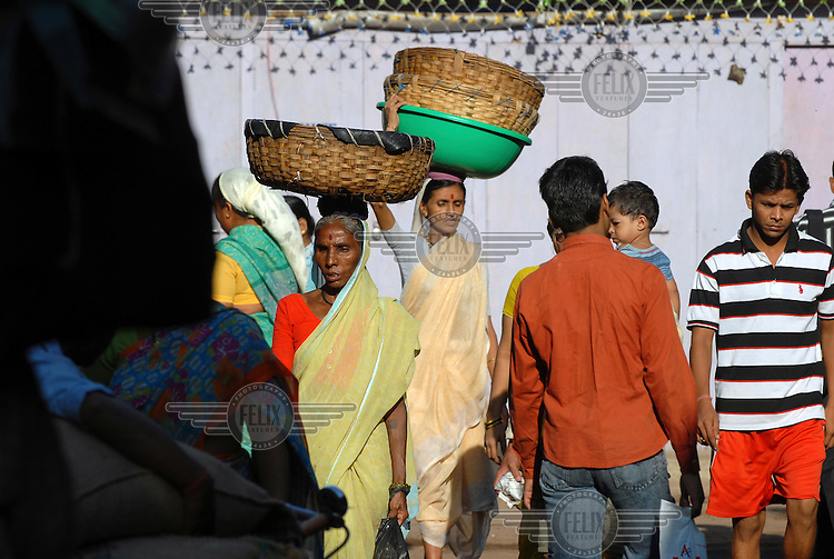Women carry baskets on their heads through busy fisherman's shanty village in Colaba, central Mumbai.