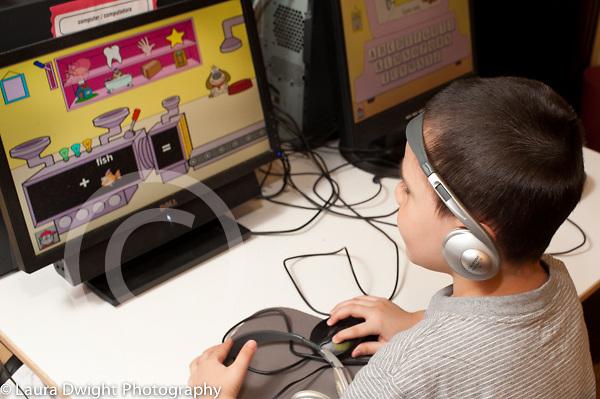 Education Preschool 3-4 year olds boy using computer to play educational game wearing headphones