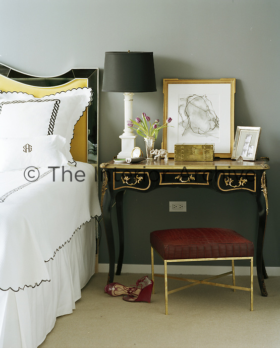 An elegant Louis XVI style desk makes the perfect bedside/dressing table. Monogrammed, scalloped bedding and glints of gold bring a touch of luxury to the bedroom