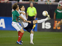 Clint Dempsey kicks the ball in front of Gerdo Torrado, left, during a 2-0 victory over Mexico, in Glendale, AZ, Wednesday, Feb. 7, 2006.