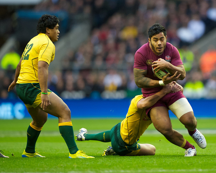 Manu Tuilagi of England is tackled by Nick Phipps of Australia during the Cook Cup between England and Australia, part of the QBE International series, at Twickenham on Saturday 17th November 2012 (Photo by Rob Munro)