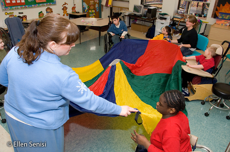 MR / Albany, NY.Langan School at Center for Disability Services .Ungraded private school which serves individuals with multiple disabilities.Children with mixed disabilities (including cerebral palsy and muscular distrophy) use parachute to develop coordination and grasping skills while playing. They are helped by teaching assistants..MR: AH-cfds.© Ellen B. Senisi