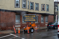 """A temporary sign reads """"Practice Social Distancing"""" during the ongoing Coronavirus (COVID-19) global pandemic in Chelsea, Massachusetts, on Mon., April 27, 2020. Chelsea, Mass., is one of the hardest hit communities in Massachusetts with high infection and death rates. As much as 80% of the population works in so-called """"essential jobs,"""" meaning that they continue to work during shelter-in-place orders."""