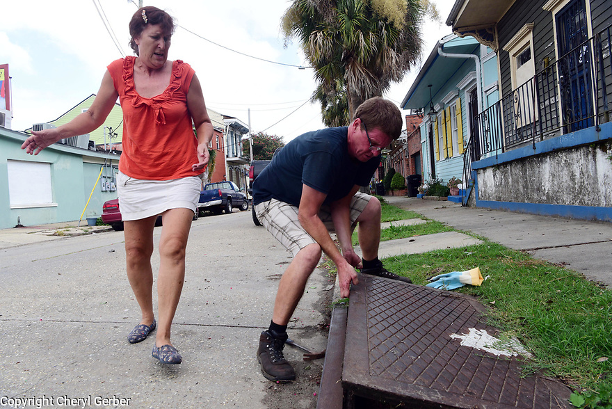 Betsy Rayner, resident of Marigny neighborhood in New Orleans,  gets help from Dave Hastings cleaning out clogged catch basins ahead of Tropical Storm Barry, which is expected to make landfall as a Category 1 hurricane on Sat., in New Orleans, Fri., July, 12, 2019.