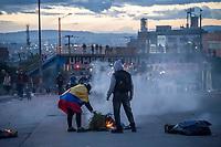 BOGOTA - COLOMBIA, 20-07-2021: Un grupo de jóvenes de primera y miembros del ESMAD de la policía se enfrentan durante los disturbios en el sector de Usme hoy, 20 de julio de 2021, en Bogotá durante la conmemoración del día de independencia de Colombia en el cual siguen las protestas del paro nacional que nuevamente convocó movilizaciones para protestar por el gobierno del presidente Duque. / A group of young people ofb the front line await the action of members of the ESMAD  of the police in the Usme sector today, July 20, 2021, in Bogotá during the commemoration of Colombia's independence day in which the protests of the national strike that again called mobilizations to protest the government of President Duque. Photo: VizzorImage / Diego Cuevas / Cont. Photo: VizzorImage / Diego Cuevas / Cont