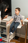 Two year old toddler boy sitting on high chair for time out gesturing and talking to his mother who is enforcing discipline