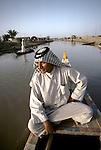 Marsh Arabs. Southern Iraq.  Marsh Arab man in boat with  adobe homes  banks of river Tigris. Haur al Mamar or Haur al-Hamar marsh collectively known now as Hammar marshes Iraq 1984