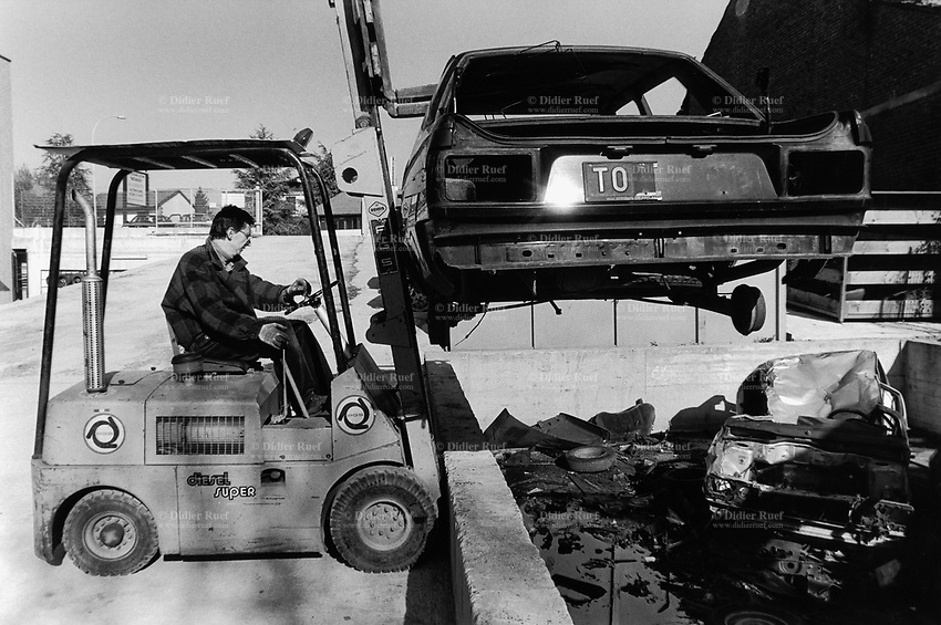 Italy. Torino Region. Moncalieri. Cars scrapyard. Derelict motor vehicles. A worker loads with a crane derelict cars on a storing place. The cars' coachworks will later be ground down and the metals recycle. © 1993 Didier Ruef