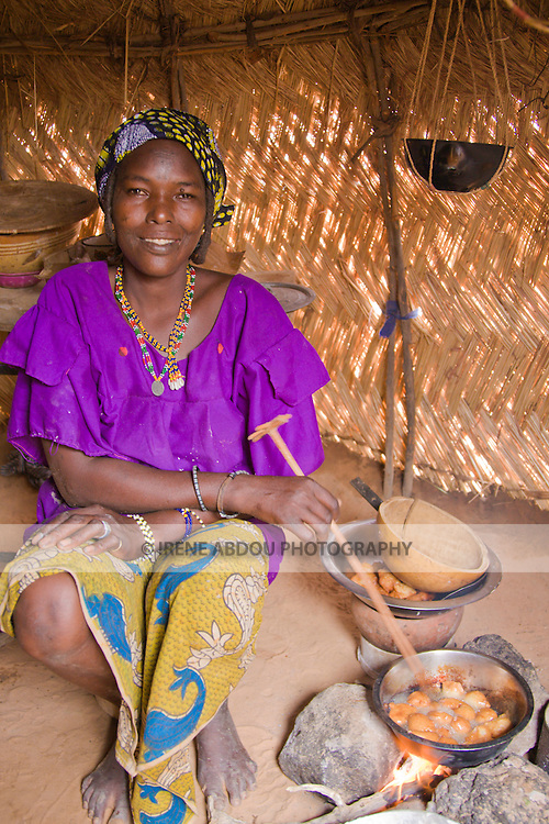 """A woman in the small village of Bele Kwara in southwestern Niger cooks """"fari masas"""" inside her traditional straw house.  The fari masas will be dipped in a bit of sugar and eaten for breakfast."""