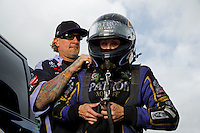 Aug 31, 2014; Clermont, IN, USA; NHRA funny car driver Alexis DeJoria (right) is assisted with putting on her safety gear by husband, television personality Jesse James during qualifying for the US Nationals at Lucas Oil Raceway. Mandatory Credit: Mark J. Rebilas-USA TODAY Sports