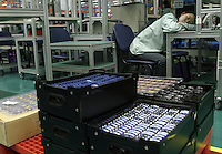 A female worker takes a sound nap near crates holding mobile phone parts at the Ninbo Bird factory in Fenghua, China. The stiff competition from both domestic and foreign brands in an already-saturated Chinese market has prompted the company to start its own Research and Development centre and seek markets in countries like India..31-OCT-03