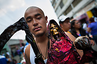A Mexican worshipper of Santa Muerte (Saint Death) holds a sacred figurine during a religious pilgrimage to the shrine in Tepito, a violent neighborhood of Mexico City, Mexico, 1 May 2011. The religious cult of Santa Muerte is a syncretic fusion of Aztec death worship rituals and Catholic beliefs. Born in lower-class neighborhoods of Mexico City, it has always been closely associated with crime. In the past decades, original Santa Muerte's followers (such as prostitutes, pickpockets and street drug traffickers) have merged with thousands of ordinary Mexican Catholics. The Saint Death veneration, offering a spiritual way out of hardship in the modern society, has rapidly expanded. Although the Catholic Church considers the Santa Muerte's followers as devil worshippers, on the first day of every month, crowds of believers in Saint Death fill the streets of Tepito. Holding skeletal figurines of Holy Death clothed in a long robe, they pray for power healing, protection and favors and make petitions to 'La Santísima Muerte', who reputedly can make life-saving miracles.