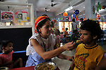 A Volunteer feeding a physically chalanged child at Sishu Bhavan, which is the house for children founded by Mother Teresa.  Kolkata, West Bengal, India. 18th August 2010. Arindam Mukherjee